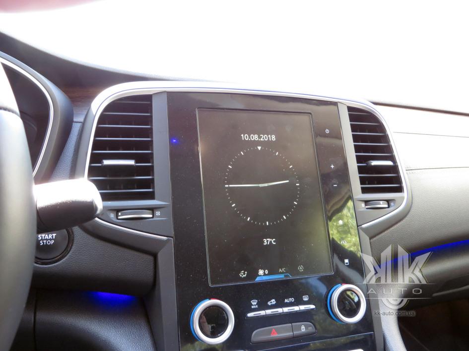 Мультимедійна система Renault Talisman нам уже знайома за іншими топовими моделями французької марки. Традиційно у фоновий режим виведено зображення аналогового годинника, дату над ним і температуру зовнішнього повітря під ним. Сенсорні кнопки чомусь розмістили з правого боку екрану: угорі - вимкнення системи, нижче збільшення/зменшення гучності аудіосистеми, ще нижче - повернення до домашнього меню, вхід у меню допоміжних систем автомобіля, а також до меню управління конфігурацією домашньої сторінки